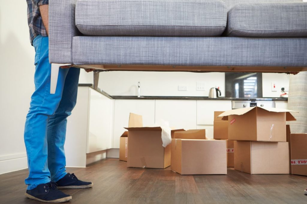 man carrying couch as he's moving in to his new home